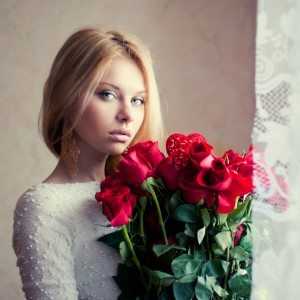 portrait of a beautiful blonde with a bouquet of roses
