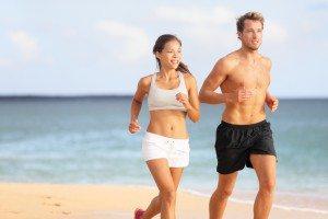 Couple running - sport runners jogging on beach
