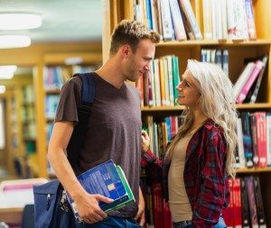 Side view of a smiling young couple against bookshelf in the library