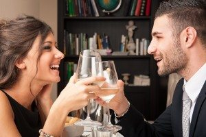 Attractive elegant young couple drinking to each others celebrat