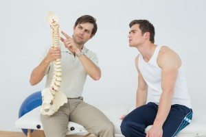 Male physiotherapist showing patient something on skeleton model in medical office