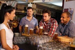 Young men flirting with bartender in pub