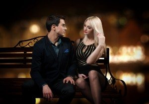 Young couple sitting on a bench, night city background