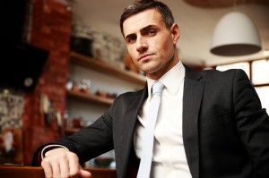Confident businessman in formal cloths resting in the kitchen