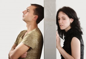 Conflict between man and woman standing on either side of a wall