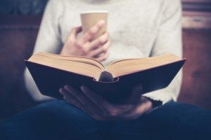 Man reading and drinking from paper cup