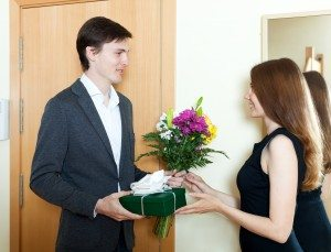 Young man giving flowers and gift to woman