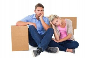 Unhappy young couple sitting beside moving boxes