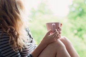 Peaceful woman relaxing at home with cup of tea or coffee