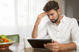 Man seems to be worried while reading information on his tablet