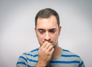 stressed mid adult man biting fingernails