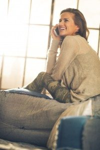 Happy young woman talking cell phone in loft apartment