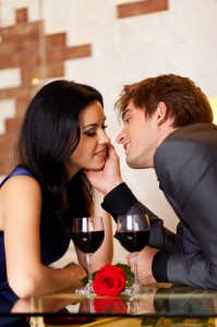 Young happy couple romantic kissing date with glass of red wine