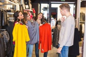 Man Helping Three Women Choosing New Clothes