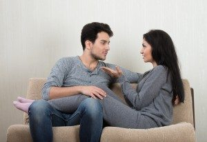 Young happy couple talking each other sitting on a sofa