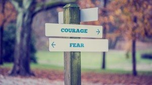 Rustic wooden sign in an autumn park with the words Courage - Fe