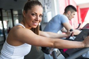 Young couple at the gym exercising on the xtrainer machines