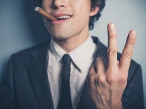 Young businessman with cigar showing rude gesture