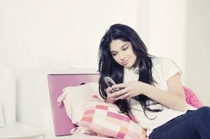 Happy teenager with mobile phone, sending text message
