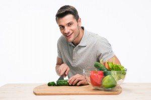 Happy man cutting vegetables