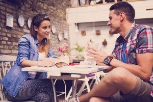 Young happy couple sitting at cafe and drinking coffee