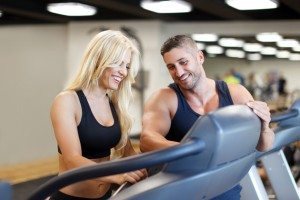 Personal trainer set difficulty on treadmill for woman