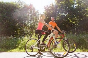 happy couple riding bicycle outdoors