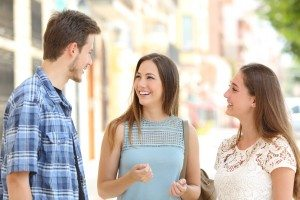 Three friends talking taking a conversation on the street