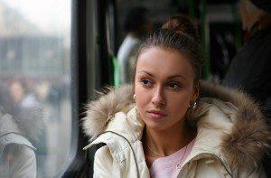 The sad beautiful girl looks in a window of the bus