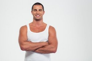 Happy muscular man standing with arms folded