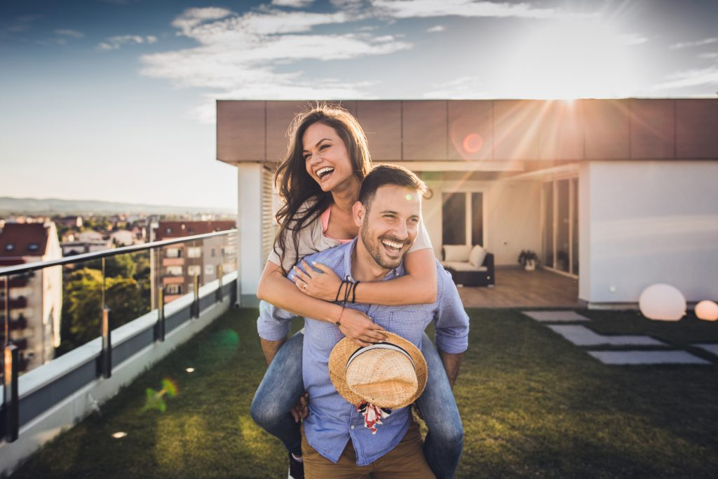 Young playful couple having fun while piggybacking on a penthouse balcony during sunny day.
