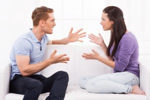 Confrontational couple. Furious young man and woman shouting at each other and gesturing while sitting on the couch