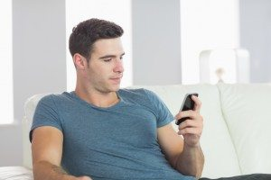 Handsome man relaxing on couch texting in bright living room