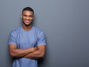 Smiling black man posing with arms crossed