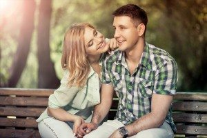 Relatioship concept. Happy young couple sitting in the park, smi